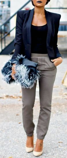 Woman on the sidewalk wearing gray pants, black top, navy blue boxy blazer and pointy white stiletto heels